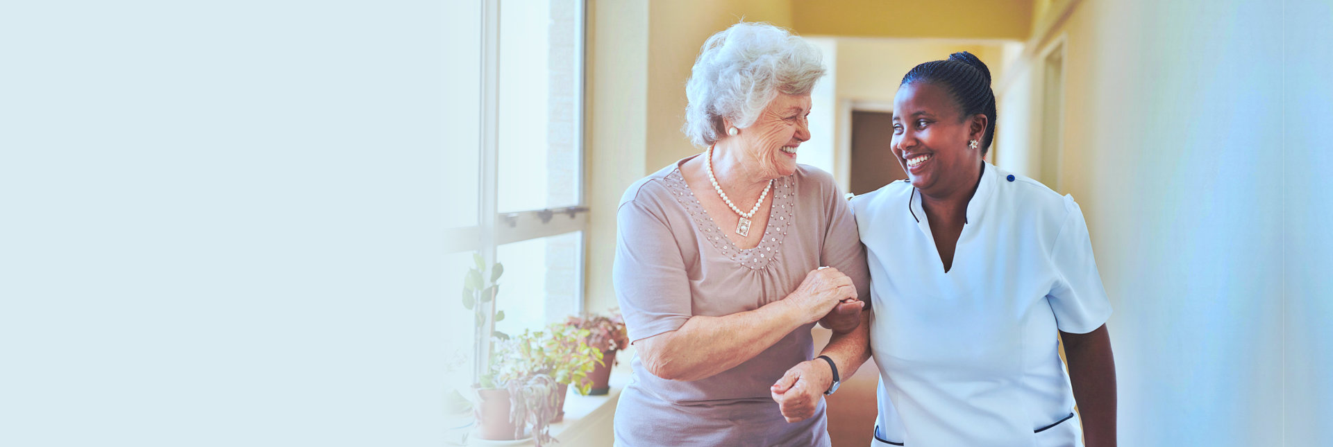 caregiver and elderly woman happily talking