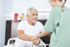 caregiver assists the senior man